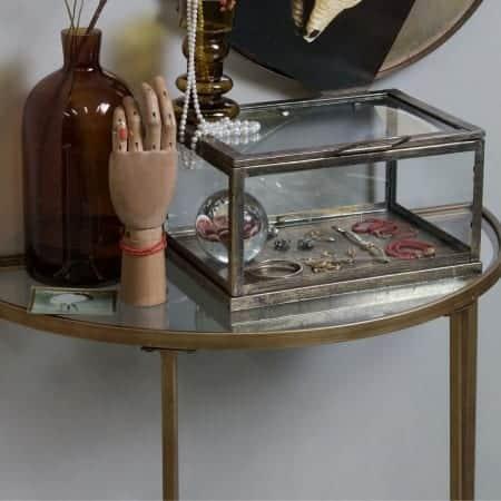 Smalle sidetable met een vaas, sierradendoos, handmodel en spiegel erboven