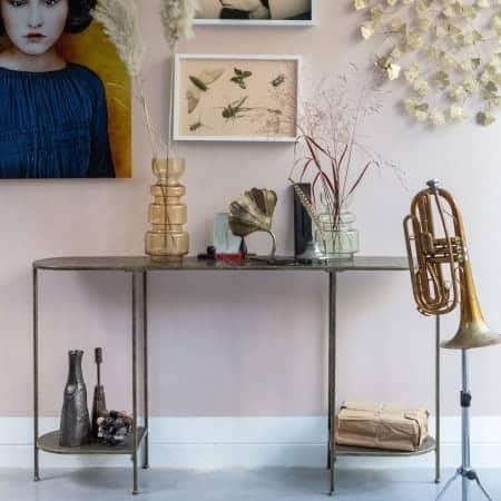 Smalle sidetable met diverse decoratieitems erop, een trompet op standaard ernaast en diverse schilderijen erboven