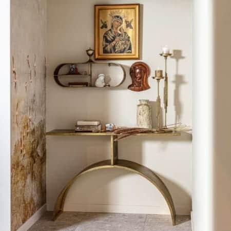 Smalle sidetable in een hal. Met schilderijen en iconen erboven, kraarsenstandaards, een vaas en boeken er op.